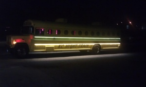 Night view of the Mellow Yellow Party Bus on the driver's side