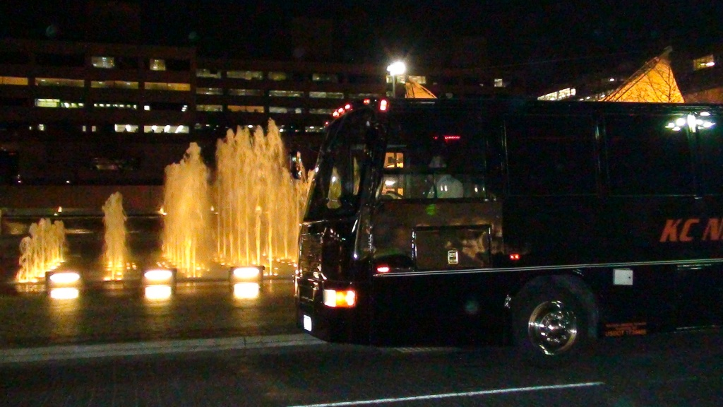 Night scene of Black VIP Party Bus parked in front of the Crown Center fountain